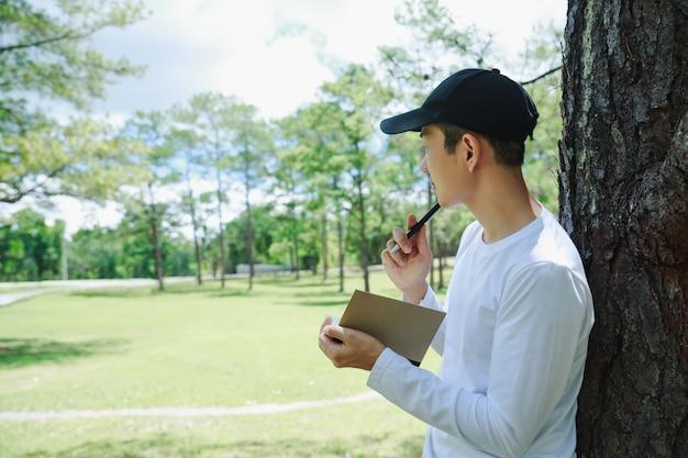 Homem asiático que está e que escreve a nota sob o pinheiro.