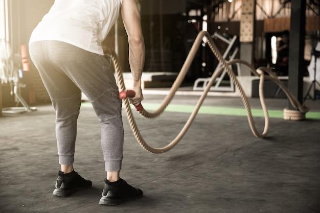 Homem asiático que exercita o homem que faz junto o exercício da corda que dá certo os braços e cardio para exercícios aptos da cruz.