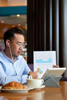 Homem asiático que explica dados no documento de negócios para seu parceiro de negócios em uma vídeo chamada