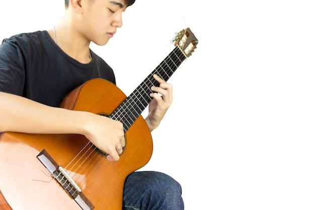 Homem asiático que joga uma guitarra clássica isolada no fundo preto.