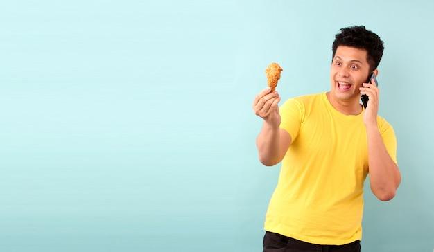 Homem asiático que mantém o telefone móvel que dá o frango frito da ordem do alimento isolado na parede azul.