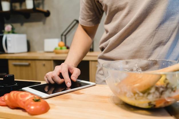 Homem asiático que olha a receita na tabuleta digital e que cozinha a comida saudável na cozinha home