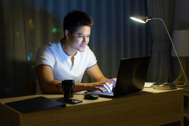 Homem asiático que trabalha em casa está sentado na frente de um computador tarde da noite.