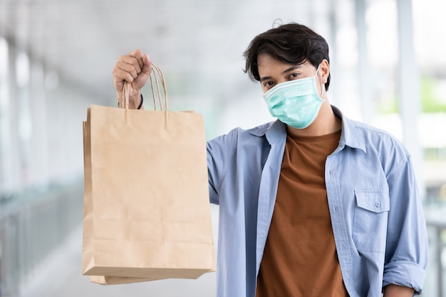 Homem asiático que veste a máscara protetora protetora que guarda o saco de compras durante o surto de doença de coronavírus, novo estilo de vida normal.