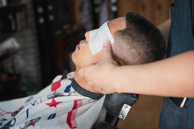 Homem asiático recebendo massagem na cabeça após terminar o corte de cabelo pelo barbeiro profissional na barbearia.