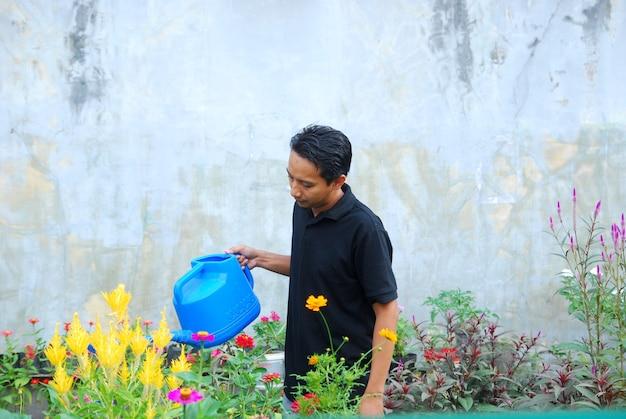 Homem asiático regando plantas no jardim