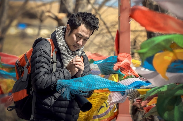 Homem asiático são oração com bandeiras de oração, banner de bênçãos tibetanas.