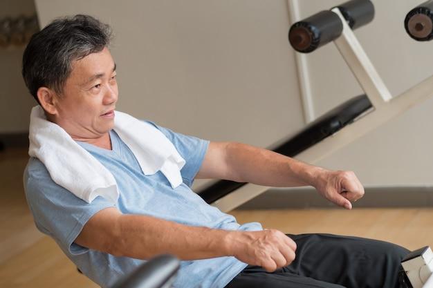 Homem asiático saudável, feliz, sorridente, positivo, bem-estar sênior malhando músculo abdominal