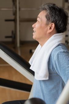 Homem asiático saudável, feliz, sorridente, positivo, bem-estar sênior malhando na academia