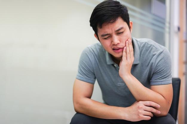 Homem asiático se sentindo ferido de sintoma de dor de dente