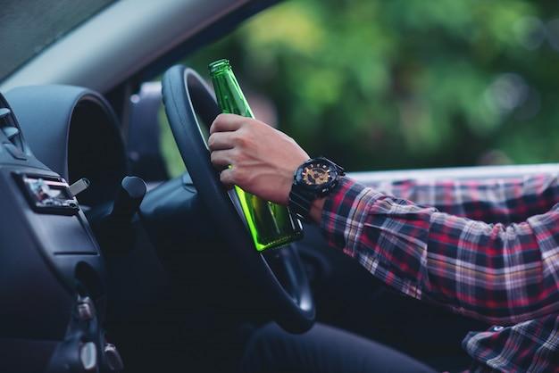 Homem asiático segura uma garrafa de cerveja enquanto está dirigindo um carro