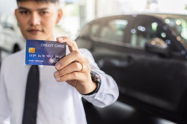 Homem asiático, segurando, cartão crédito, para, car, obscurecido, bokeh, fundo, e-shopping, marketing, digital