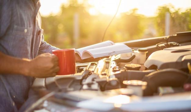 Homem asiático segurando e lendo o manual do usuário do carro para verificar o motor do carro moderno