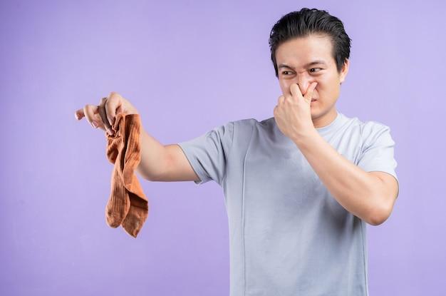 Homem asiático segurando meias em roxo