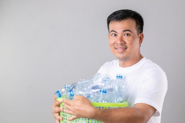 Homem asiático segurando muitas garrafas de água transparente vazias