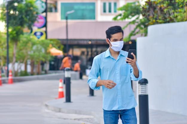 Homem asiático, segurando o telefone móvel esperto use máscara facial proteger vírus corona pm2.5 andando na rua novo normal social distanciamento