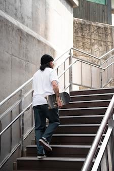 Homem asiático segurando seu skate enquanto caminha na escada