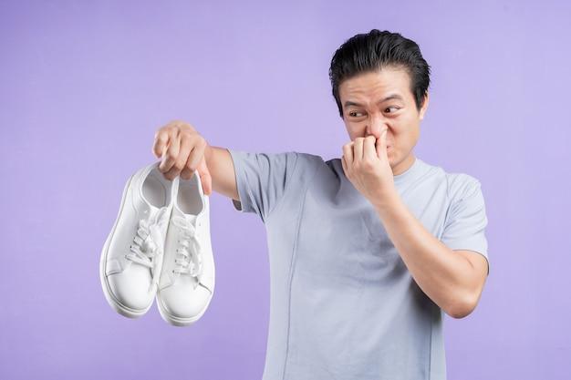 Homem asiático segurando tênis em roxo