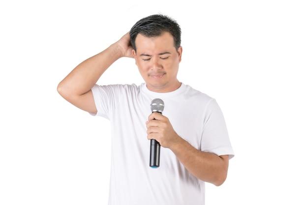 Homem asiático segurando um microfone sem fio e esquecendo o que dizer