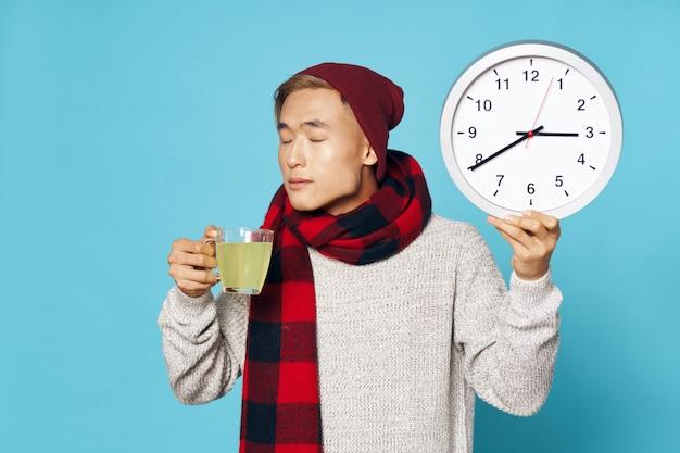 Homem asiático, segurando um relógio, e, bebendo, medicina