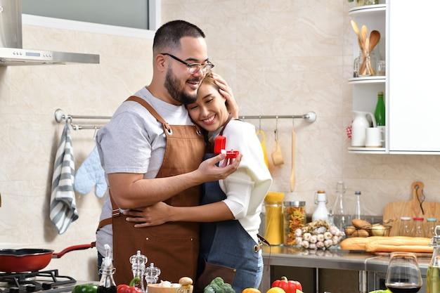 Homem asiático segurando uma caixa vermelha com um anel fazendo casamento com a namorada na cozinha