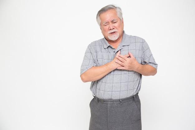 Homem asiático sênior com dor no coração, isolada no fundo branco.
