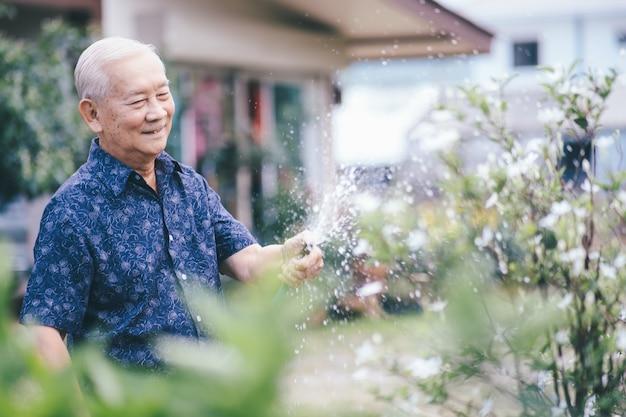 Homem asiático sênior feliz em seu jardim. feliz idade de aposentadoria.
