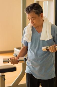 Homem asiático sênior malhando, musculação com halteres