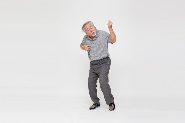 Homem asiático sênior ouvindo música com fones de ouvido e dançando isolado no fundo branco