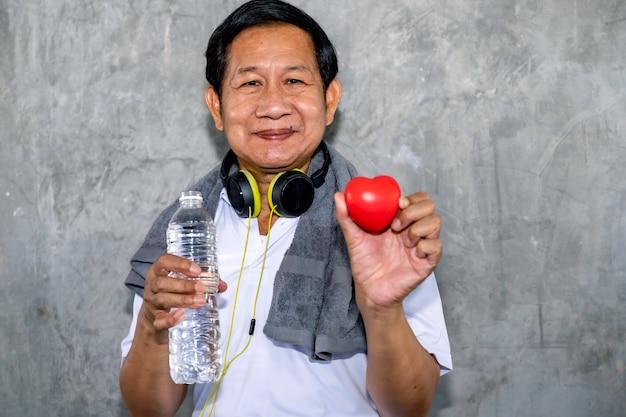 Homem asiático sênior que sorri no sportswear segurando coração vermelho. boa vida.