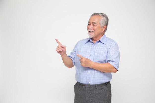Homem asiático sênior sorrindo e apontando para o espaço vazio da cópia, isolado no fundo branco