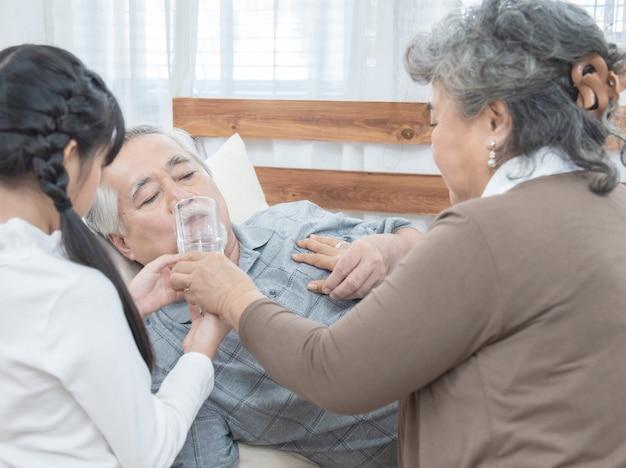 Homem asiático sênior tomando medicamentos e água potável enquanto deitar no sofá em casa