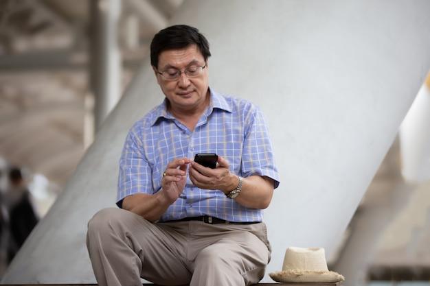 Homem asiático sênior usando telefone celular enquanto está sentado ao ar livre