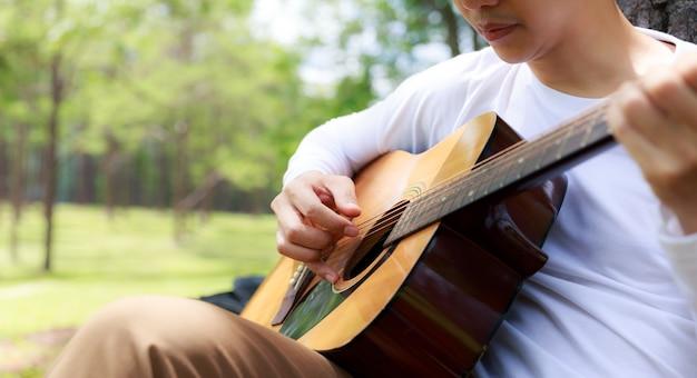 Homem asiático sentado e cantando com guitarra debaixo de pinheiro.