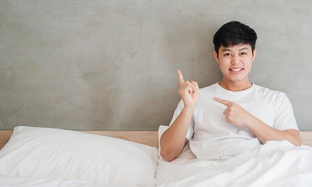 Homem asiático sentado na cama e mão apontando fundo cinza de cimento (para seu projeto)