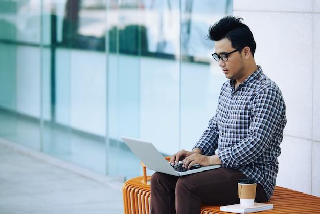 Homem asiático, sentado no banco ao ar livre, perto da parede de vidro e trabalhando no laptop