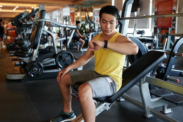 Homem asiático, sentado no banco no ginásio e olhando para o relógio de pulso
