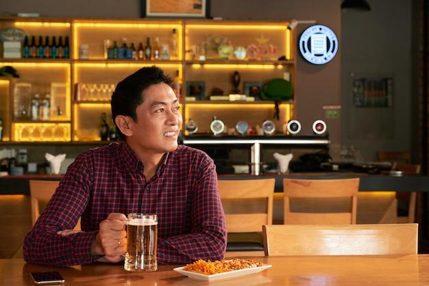 Homem asiático sentado no bar com uma caneca de cerveja e lanches e olhando alguma coisa