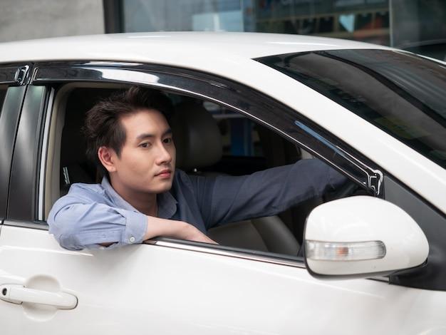 Homem asiático sentado no carro novo e mostrando as chaves do carro. automóvel de salão do homem atrativo novo que olha a janela aberta.