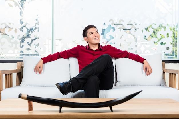 Homem asiático sentado no sofá na loja de móveis