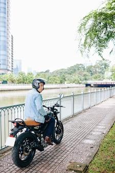 Homem asiático sério de capacete andando de moto ao longo da margem do rio e olhando para longe