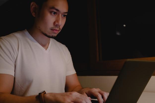 Homem asiático sério está trabalhando com o laptop à noite.