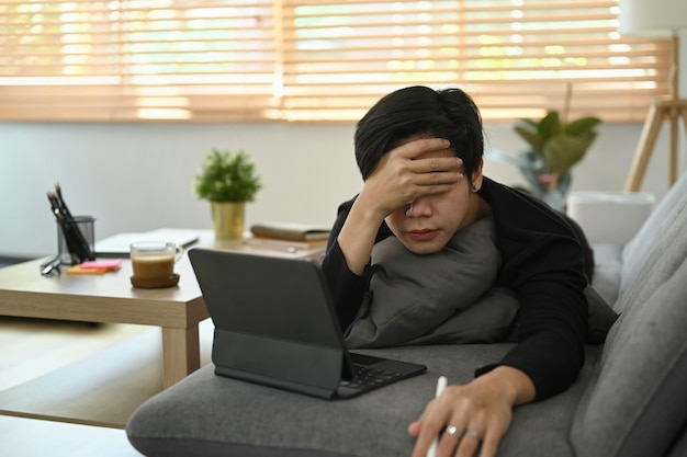 Homem asiático sobrecarregado, trabalhando com o tablet do computador no sofá.