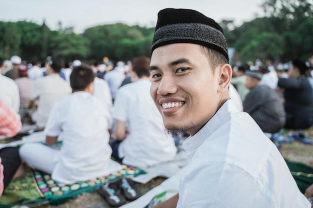 Homem asiático sorri alegremente com as orações do eid al-fitr