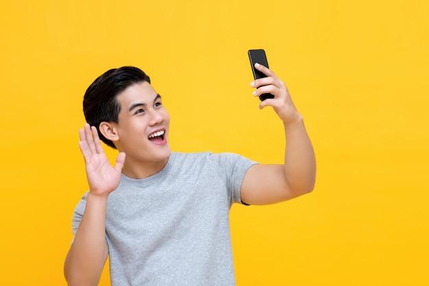 Homem asiático sorridente, acenando a mão ao fazer uma chamada de vídeo no smarphone