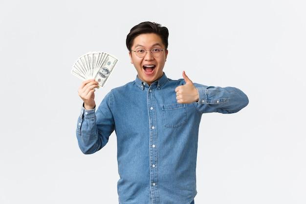 Homem asiático sorridente animado com aparelho e óculos, mostrando o polegar para cima e acenando com dinheiro, recebe o cheque de pagamento ...
