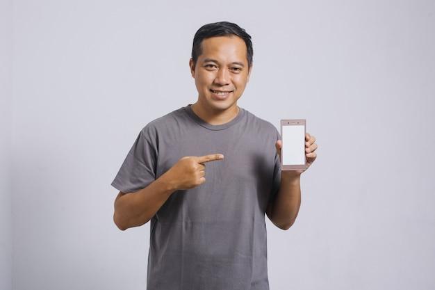 Homem asiático sorridente apontando seu telefone inteligente com tela em branco para simulação