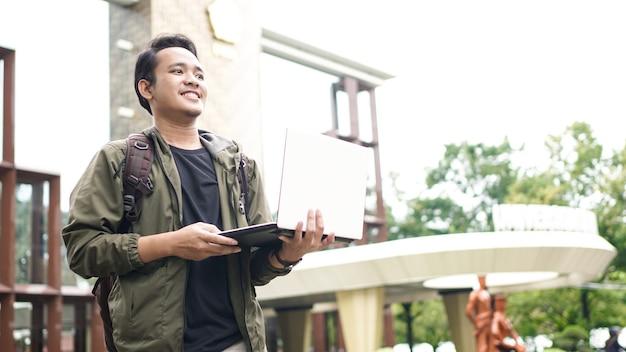 Homem asiático sorridente com uma mochila e um laptop