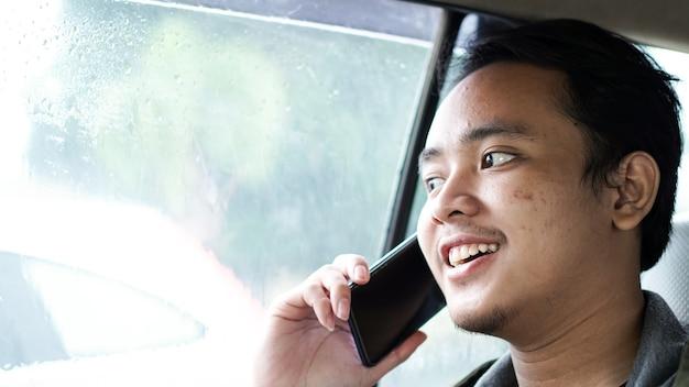 Homem asiático sorridente em um carro enquanto falava ao telefone