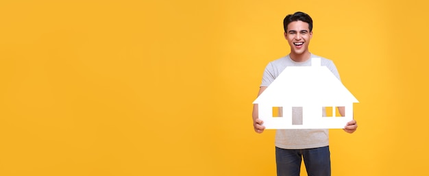 Homem asiático sorridente feliz segurando a casa de papel isolada em um fundo amarelo com espaço de cópia. fundo panorâmico.